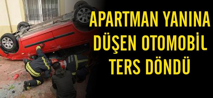 Apartman yanına düşen otomobil ters döndü